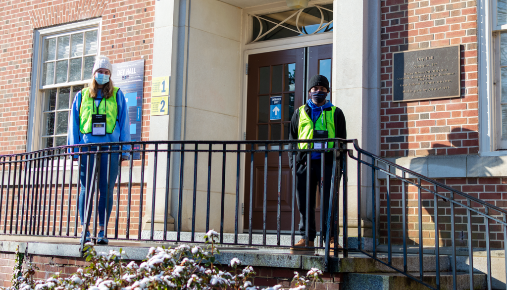 Two Carolina Together Ambassadors wearing yellow work vests and face masks stand outside of Dey Hall on UNC-Chapel Hill campus.